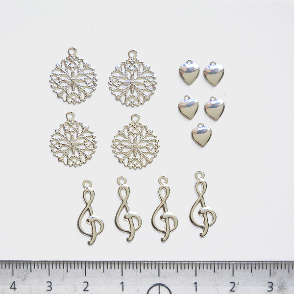 Maskotti, hopeoitua messinkiä, setti: lumihiutale, musiikkiavain, sydän, noin 5-15mm, 13 kpl kuin kuvassa