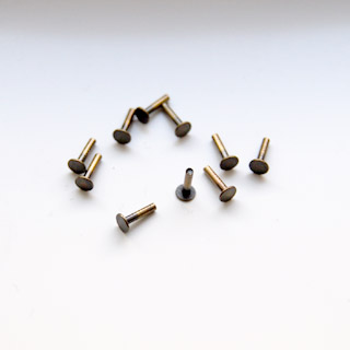 Niitti, messinkiä, antiikkipatinoitu (pronssiväri), kahden metalliosan kylmäliitokseen, noin 6x4mm, 1.3mm paksu, 10kpl
